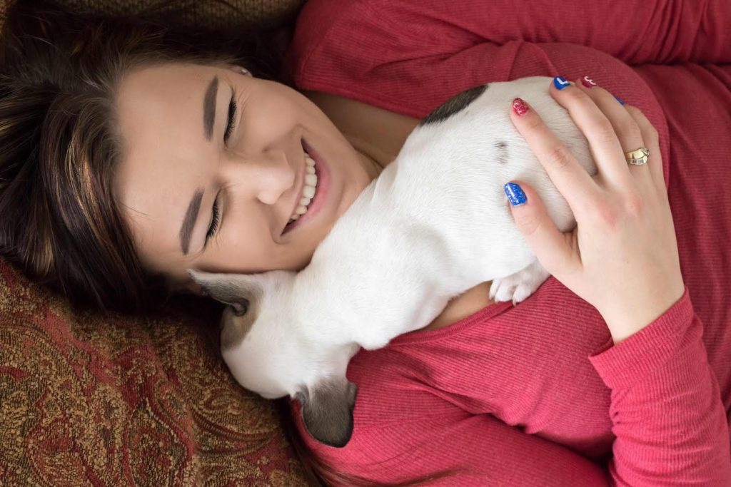A young woman snuggles with her French bulldog puppy in her Brighton, Michigan, home